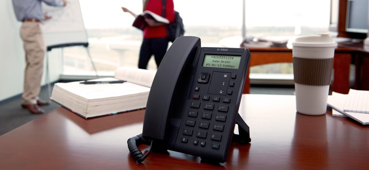 Mitel phone on desk while people talk in the background