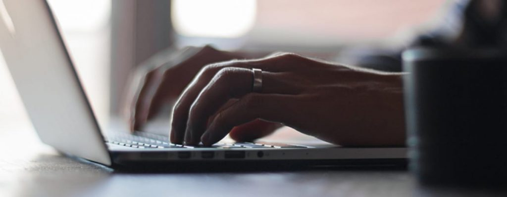 Hands typing on keyboard with wedding ring