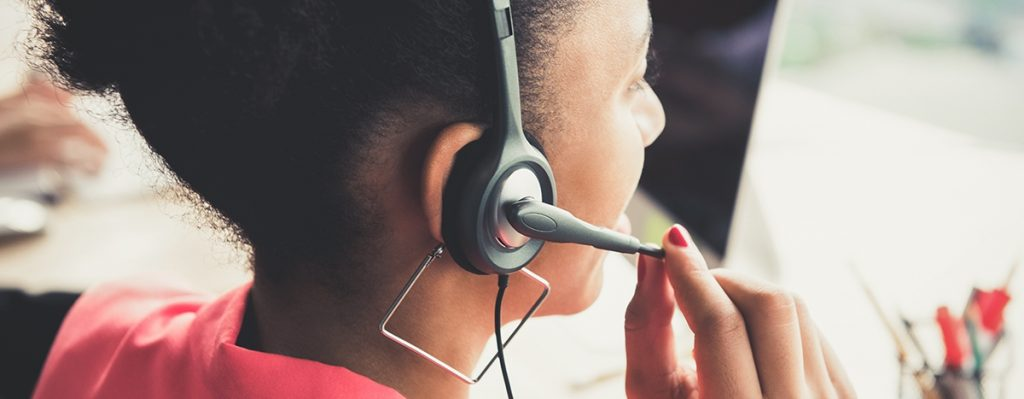 Black woman with square earrings using headset at a call center