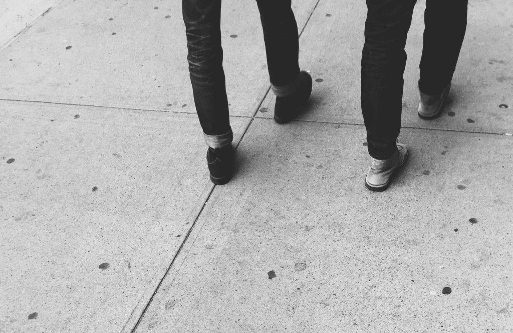 Two men walking on sidewalk with jeans and boots in black and white