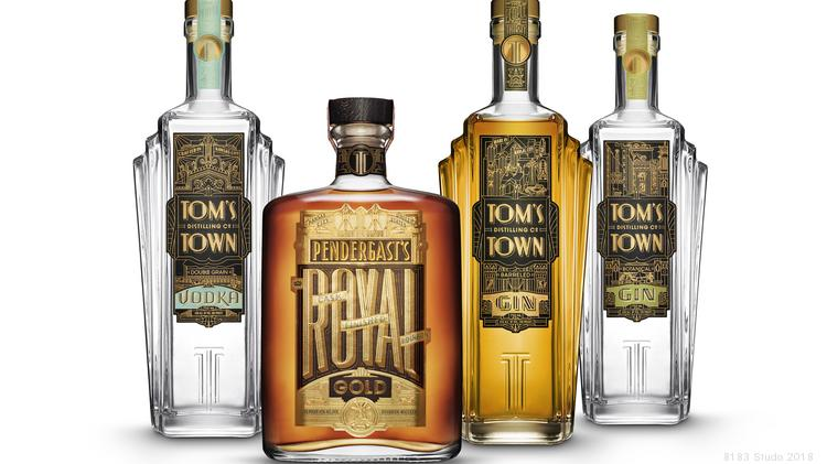 Four bottles of Tom's Town alcohol, including Gin, Whisky, and Vodka