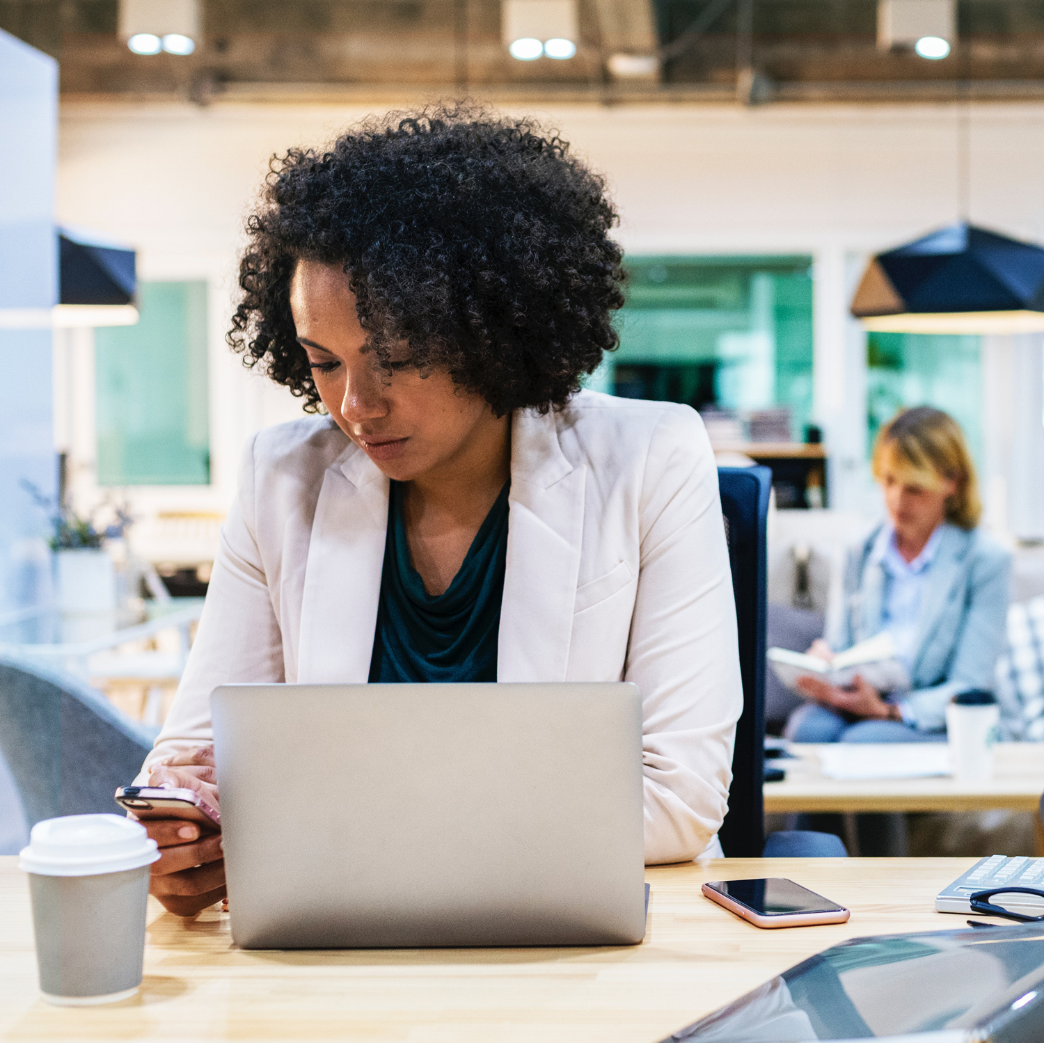 Woman setting up marketing on hold at her desk with white blazer and blue shirt