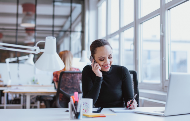 Woman in turtleneck on business call at work with white lamp