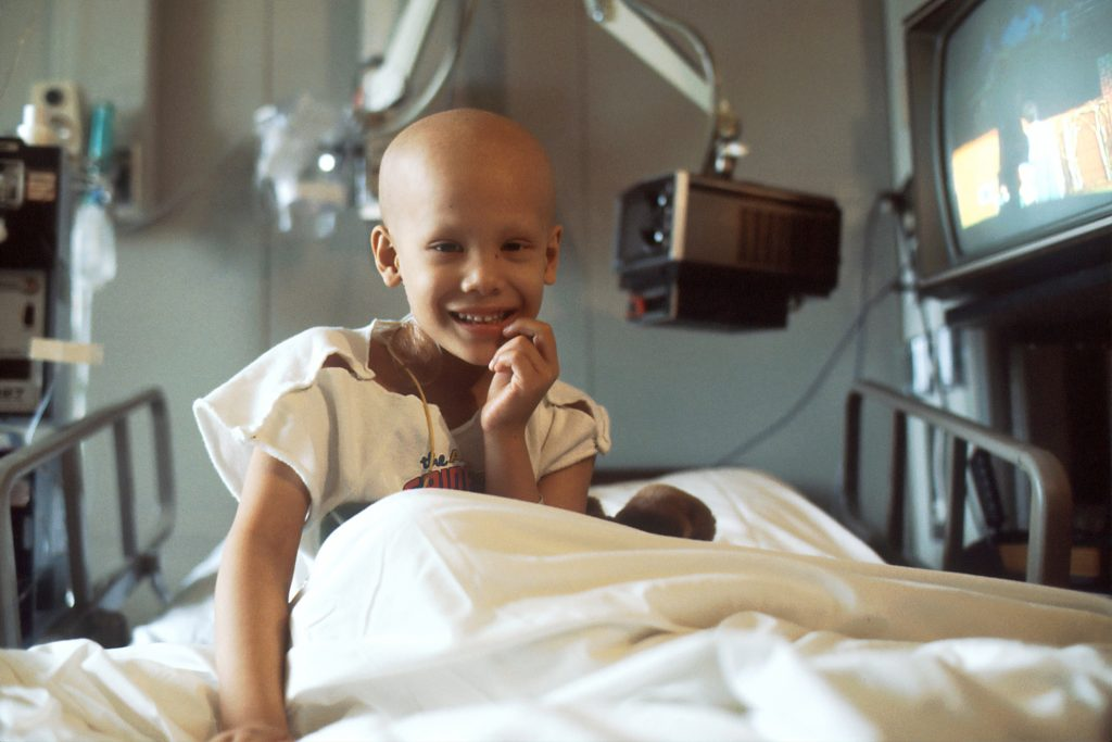 child with cancer sitting in a hospital bed