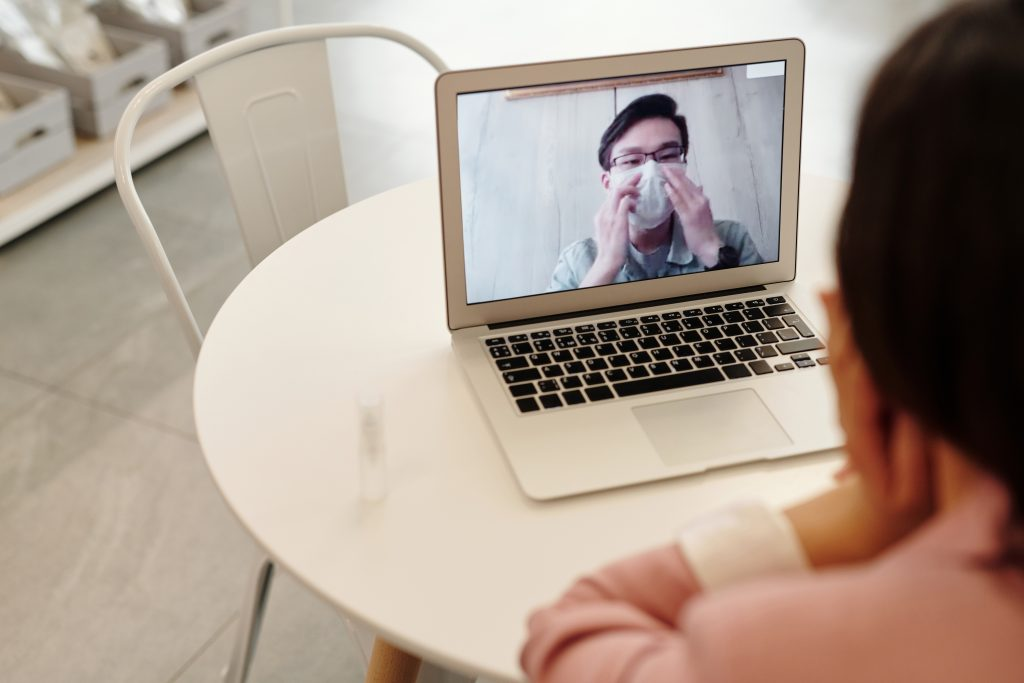 Man in mask talking to doctor on video call